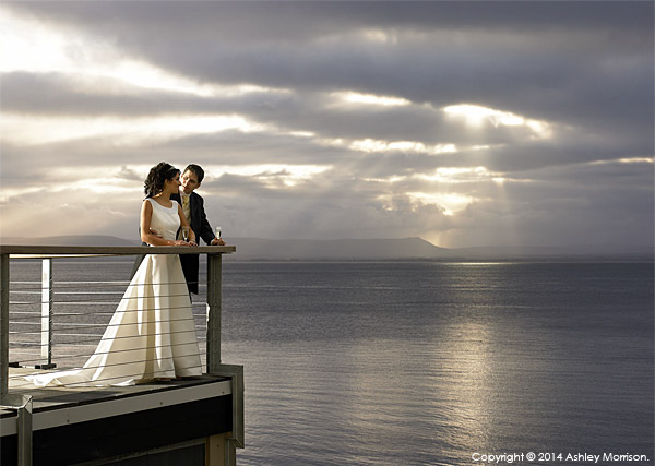 Bride & Groom standing out on the balcony at the Redcastle Hotel near the town of Moville on the Inishowen Peninsula of County Donegal.