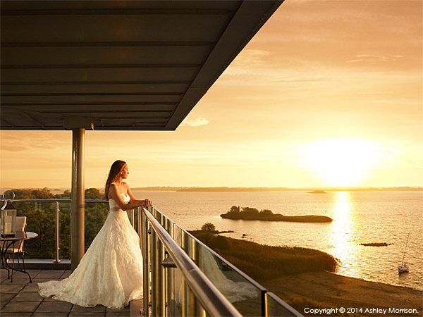 Bride standing in the balcony of Penthouse suite at the Hodson Bay Hotel near Athlone in Ireland.